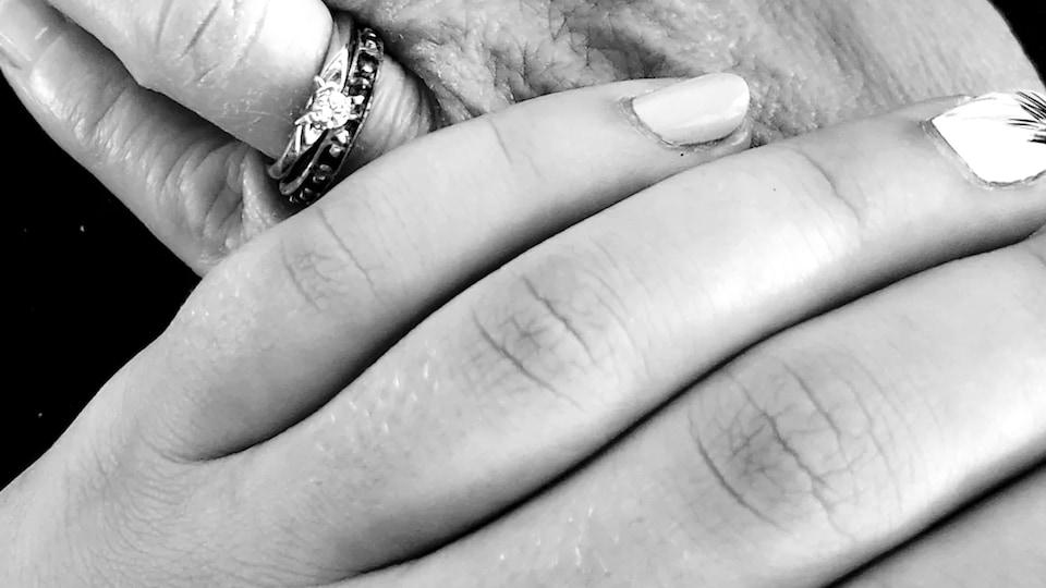 Une main jeune est posée sur une main plus âgée.