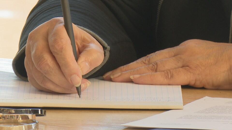 Gros plan de mains d'une femme prenant des notes.