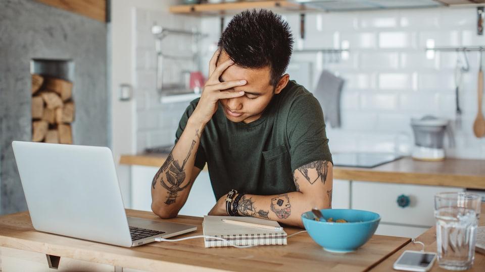 Un jeune homme devant son ordinateur.
