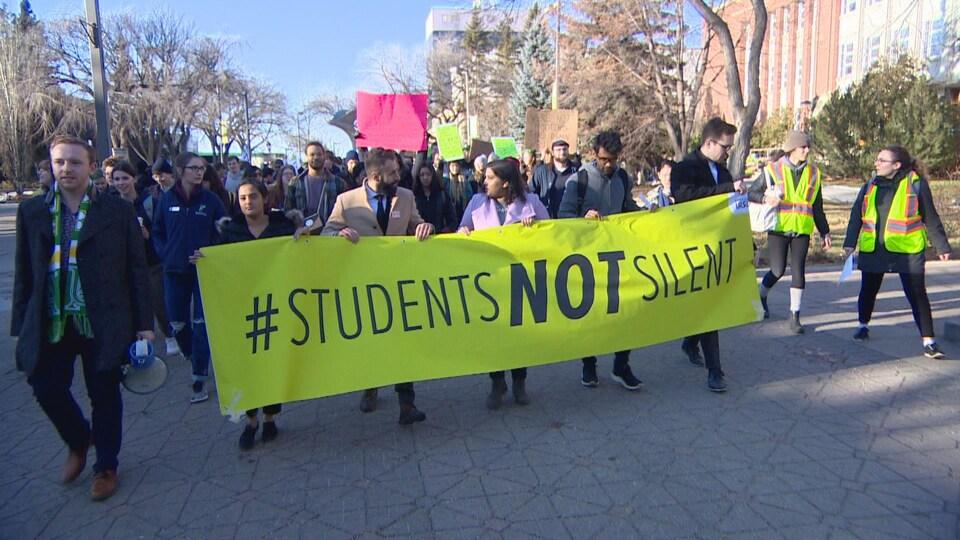 Des étudiants marchent en rangées. Le premier rang tient une large banderole. Il y est écrit en anglais : les étudiants ne seront pas silencieux.