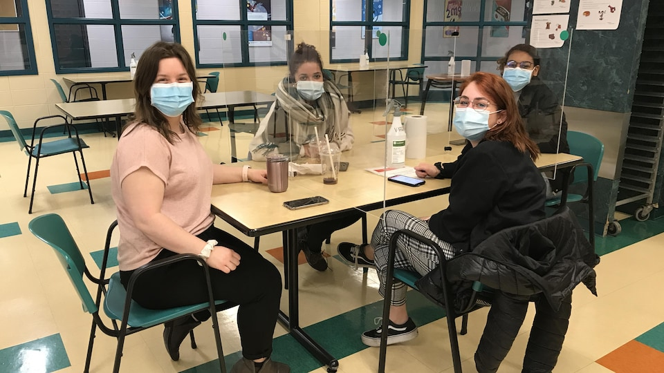 Quatre étudiantes sont assises à une table séparée en quatre sections par des plexiglas. Chacune porte un couvre-visage.