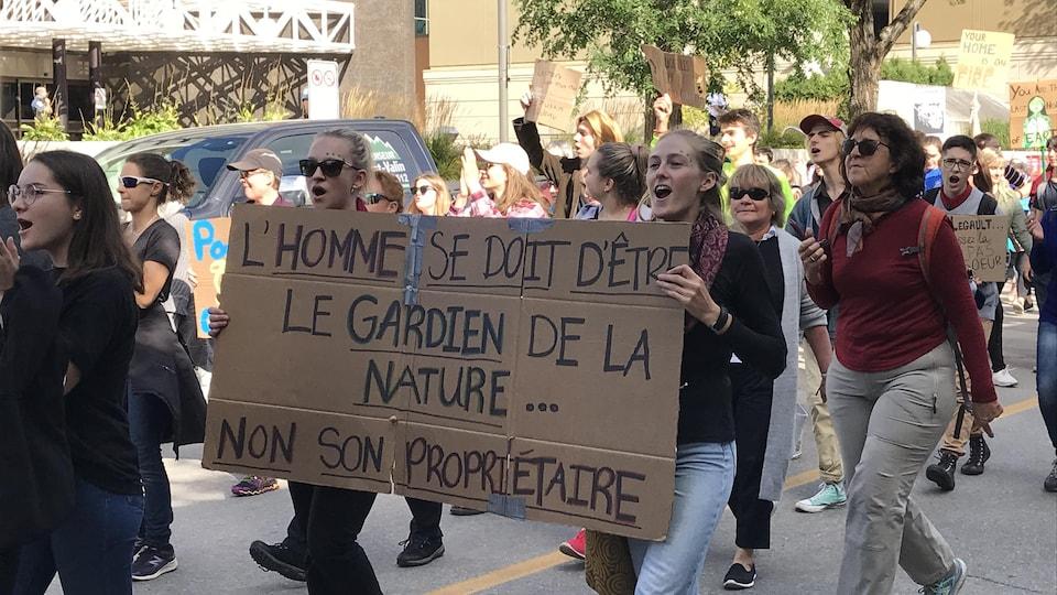 Des manifestants pour le climat avec une pancarte sur lequel il est écrit L'homme se doit d'être le gardien de la nature... non son propriétaire.