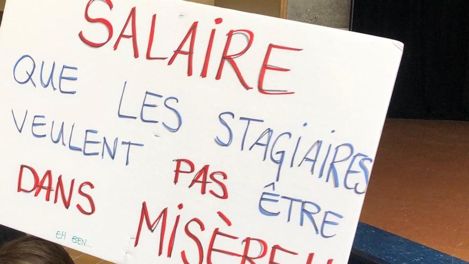 Une affiche sur laquelle on peut lire « Salaire que les stagiaires ne veulent pas être dans la misère ».