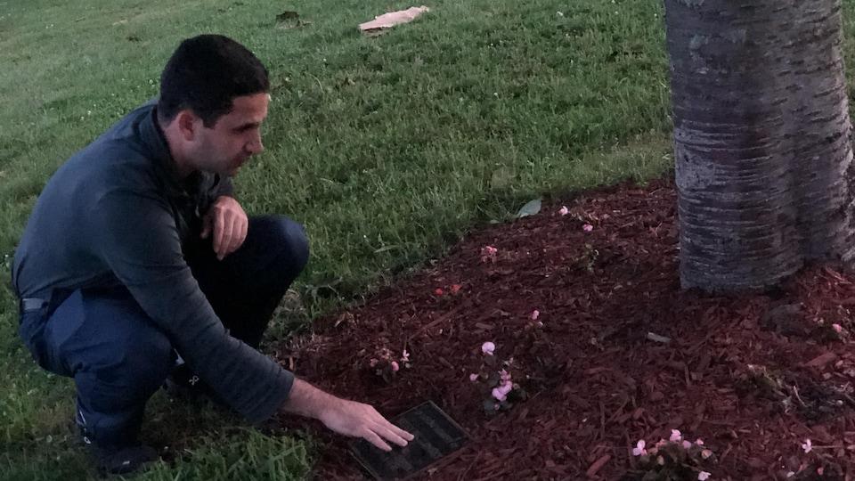 Eugene Belilovsky est agenouillé au pied d'un arbre, caressant une plaque commémorative.