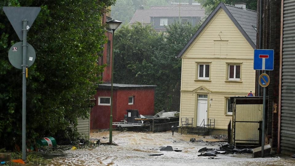 L'eau inonde une rue devant une maison.