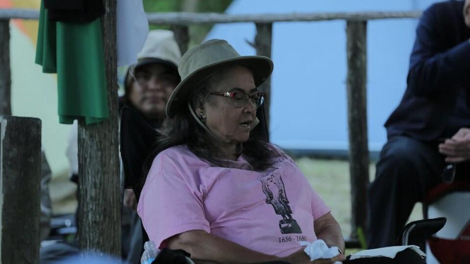 Sœur Eva Solomon assise sous un chapiteau.