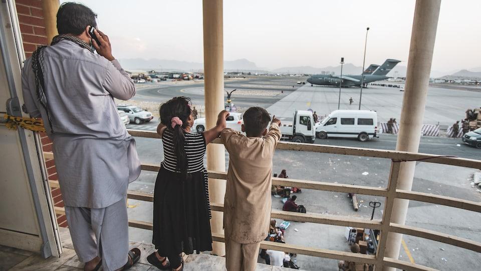 Deux enfants sur une passerelle montrent du doigt un avion sur le tarmac.