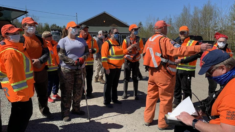 Des membres des services de secours, habillés en orange, se préparent pour un mouvement d'évacuation.