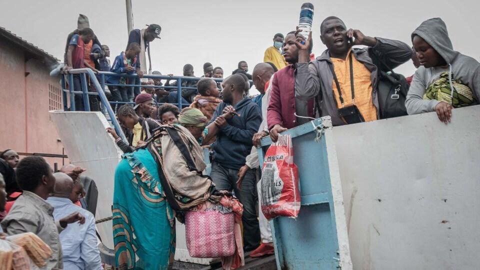 Des dizaines de personnes se massent sur un bateau, sur lequel des gens continuent d'embarquer.