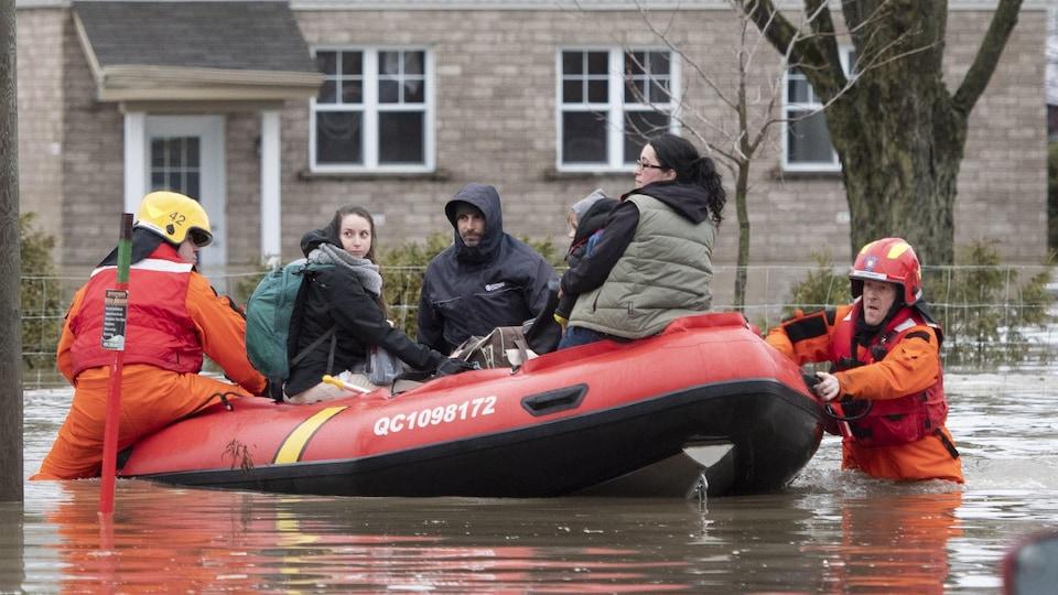Des citoyens sont évacués par des pompiers dans un bateau.