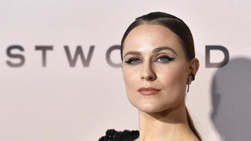L'actrice vêtue d'une robe noire prend la pose pour les caméras sur le tapis rouge d'une première de la série « Westworld », dont le titre apparaît derrière elle sur un panneau.