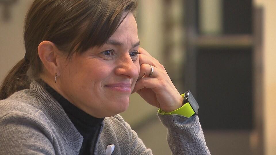 Une femme souriante avec la tête appuyée sur sa main gauche.