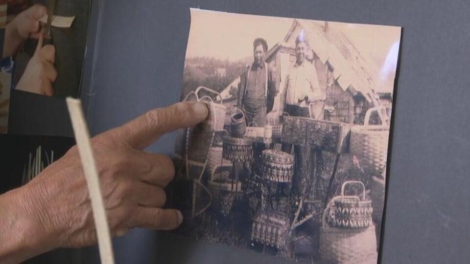 Keptin James Bernard pointe une photo en noir et blanc de son oncle, debout devant une petite remise, avec une pile de paniers complexes au premier plan.