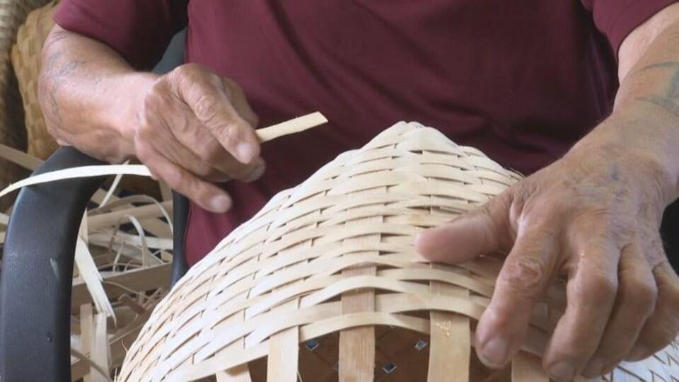 Un tisseur a dans la main des éclisses qu'il utilise pour fabriquer un panier.