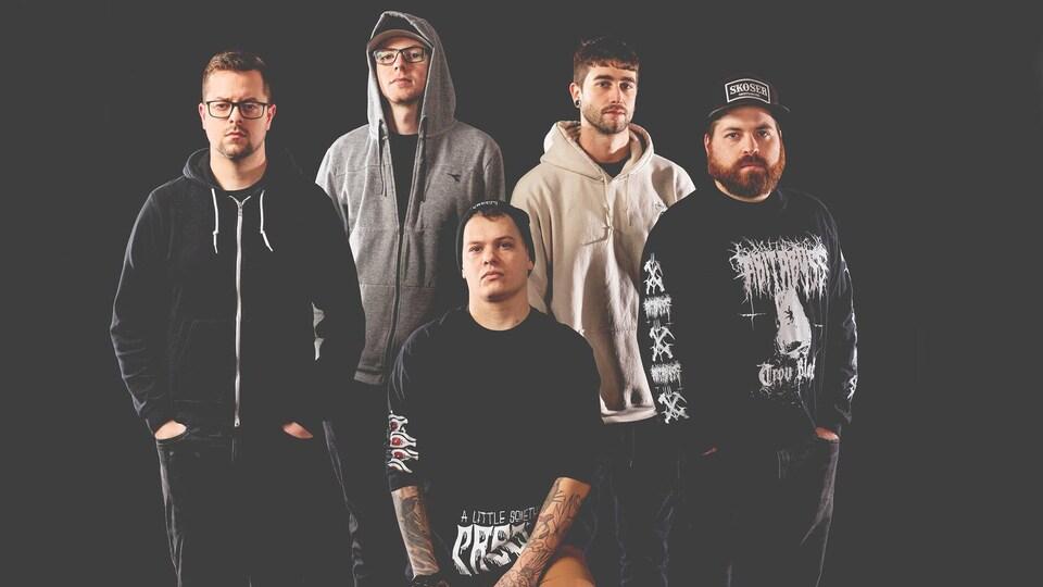 Cinq hommes d'un groupe musical posent sur un fond noir.