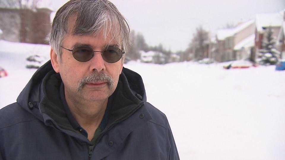 Homme l'hiver avec des lunettes de soleil dans une rue enneigée