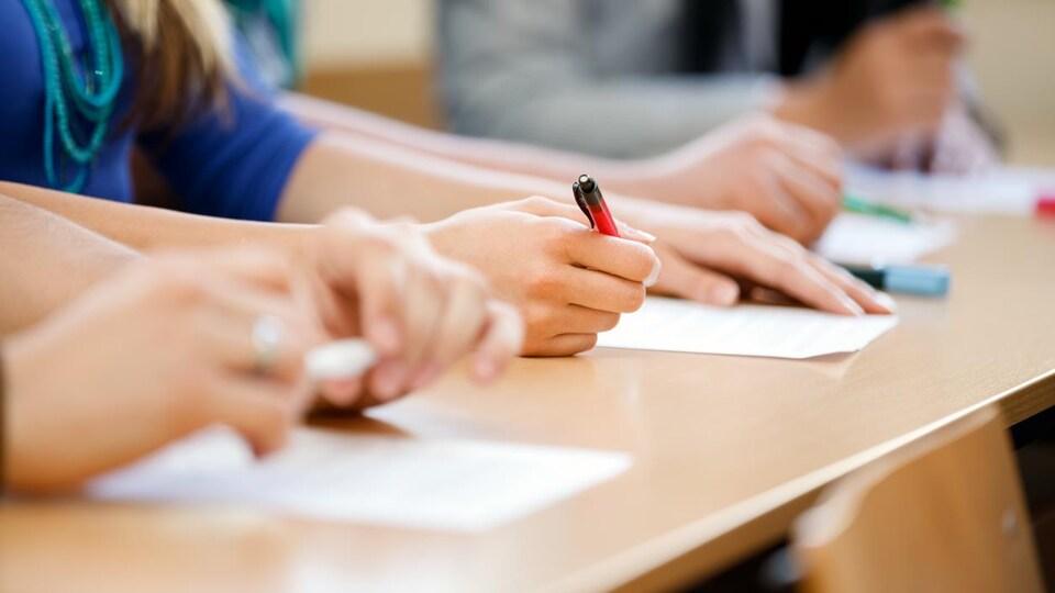 Des feuilles de papier et des crayons sont déposés sur un long bureau en bois. On voit des mains d'élèves qui répondent aux questions.