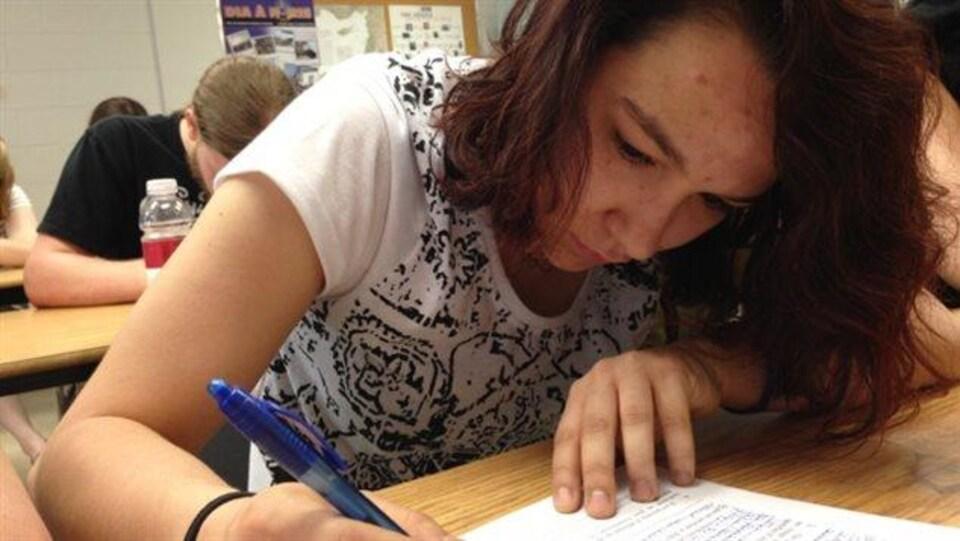Une élève du secondaire complète un examen.