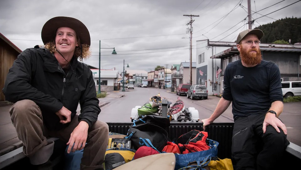 Alex Morrow et Andrew Green sont assis derrière un véhicule qui traine des kayaks.