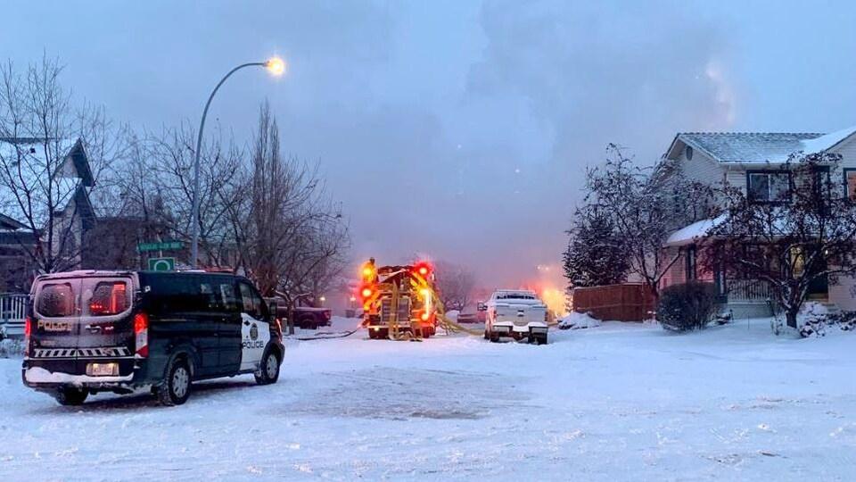 Des camions de pompiers et de la police sont garés dans une rue enneigée non loin du lieu de la déflagration à Calgary.