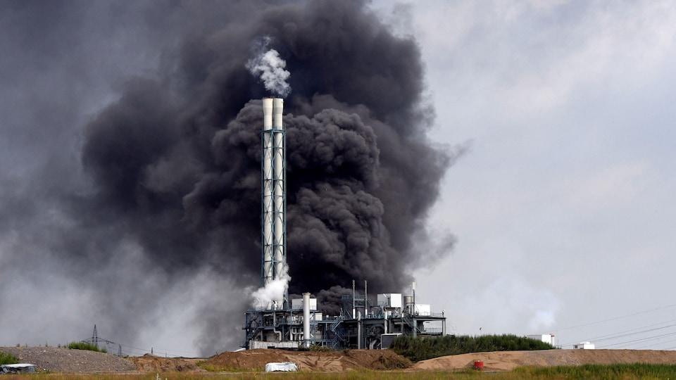 De la fumée noire s'élève dans le ciel autour de la cheminée d'un incinérateur.