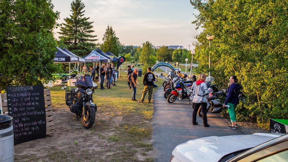 Des kiosques sont installés dans un parc où sont stationnées plusieurs motos.