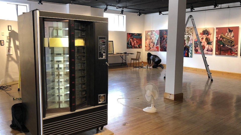 Une machine distributrice au centre d'une exposition d'oeuvres d'art visuel.