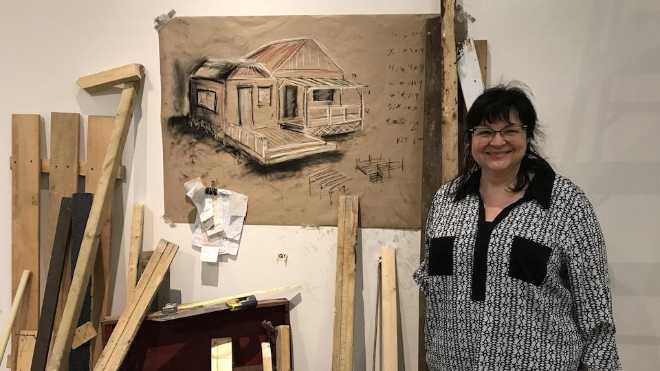 Carmelle Adam debout devant une oeuvre composée d'un dessin sur une toile, d'un coffre et de planches de bois.