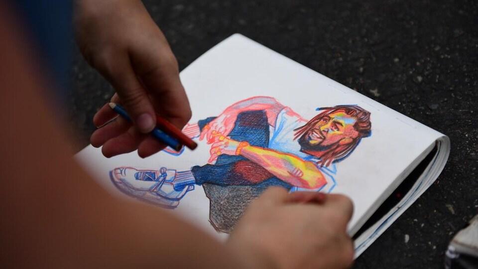 Les mains de l'artiste dessinent en couleur un homme assis.