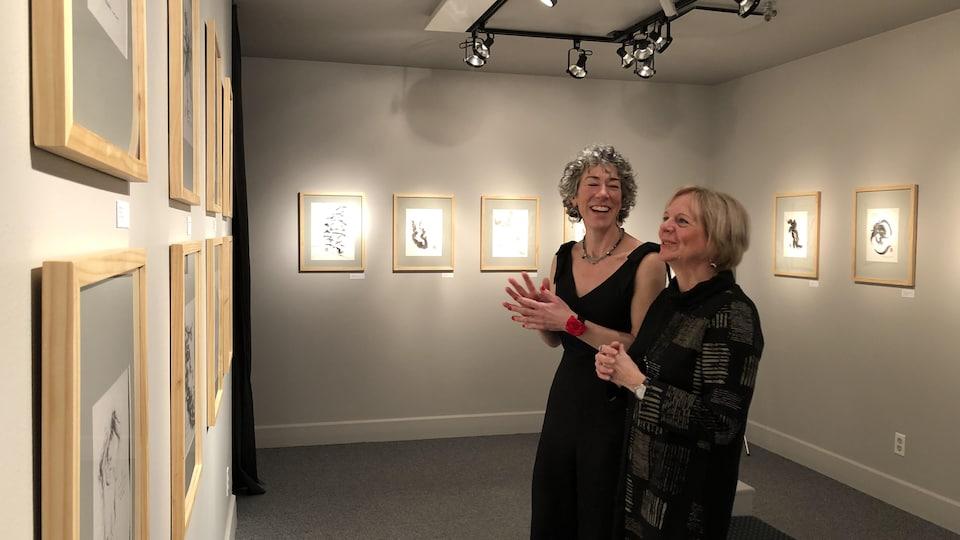 Deux femmes devant des oeuvres exposées dans une galerie d'art