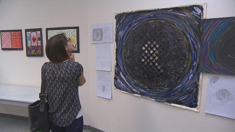 Une femme regarde une oeuvre exposée par l'organisme Les Impatients.