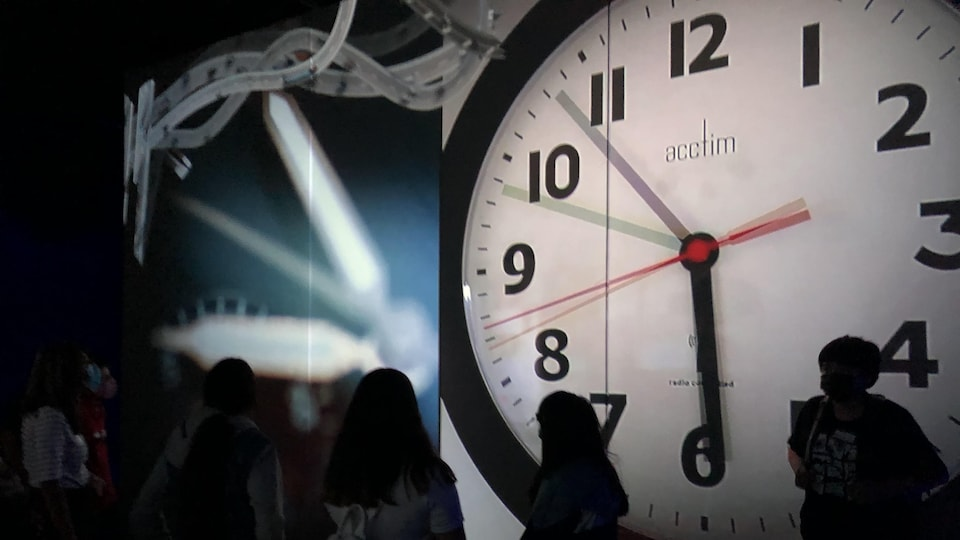 Un horloge sur un grand écran.