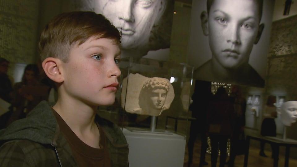 Un garçon devant une sculpture de son sosie au Musée de la civilisation