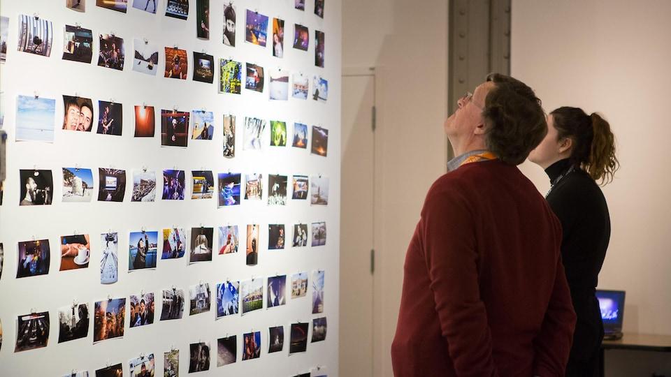Un visiteur regarde des photos accrochées au mur.