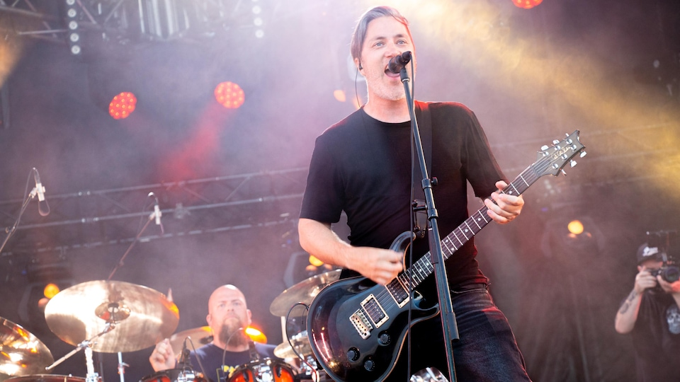 Un homme chante sur scène avec un micro devant lui et une guitare dans les mains. Un autre homme joue de la batterie derrière lui.