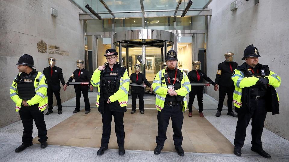 Quatre policiers sont debout devant la rangée de manifestants.
