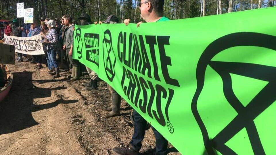 Des manifestants dressent une bannière verte d'Extinction Rebellion.