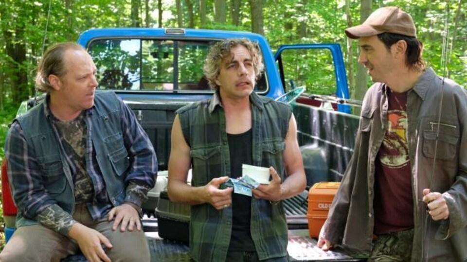 Les trois hommes discutent en arrière d'un pick-up.