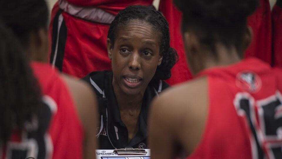 Une entraîneuse de basketball donne ses explications à ses joueuses pendant un temps d'arrêt.