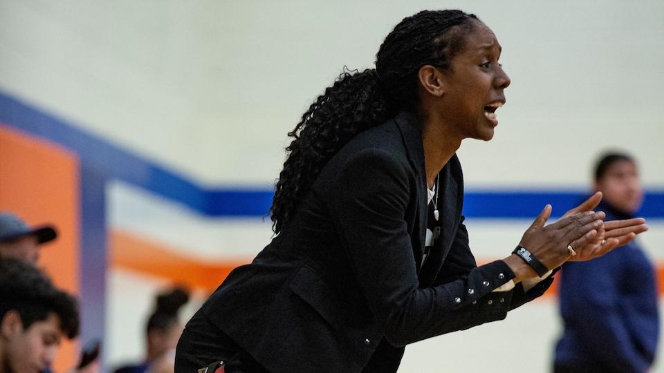 Une entraîneuse encourage ses joueurs pendant une partie de basketball.