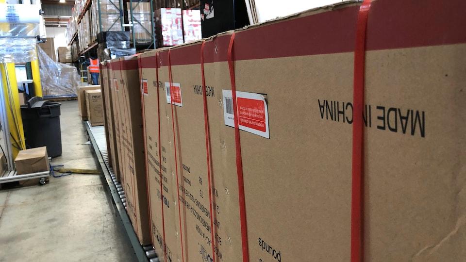 Des boîtes sur lesquelles il est inscrit « fabriqué en Chine » sont sur un convoyeur d'un entrepôt, en Californie.