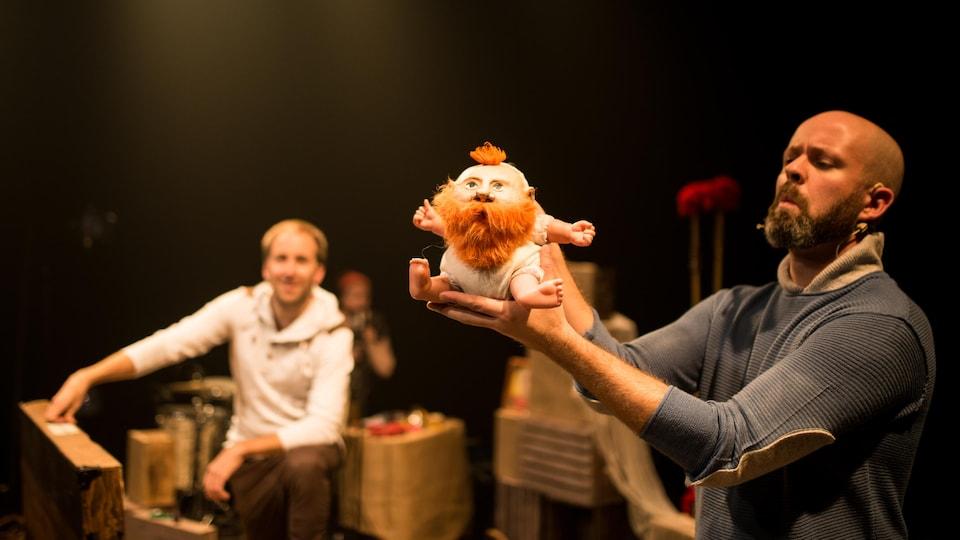 Un homme tient une marionnette sur scène.