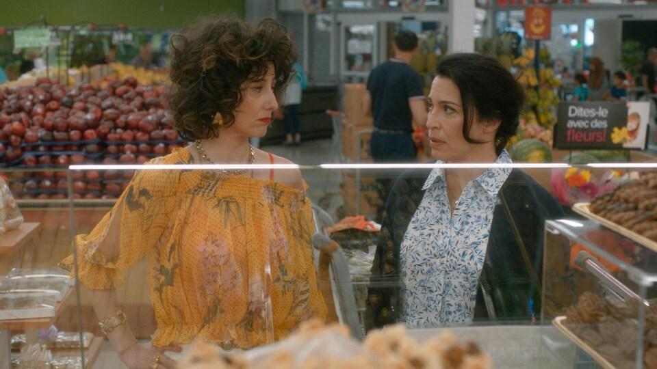 Deux femmes se regardent devant un comptoir de pâtisseries, à l'épicerie.