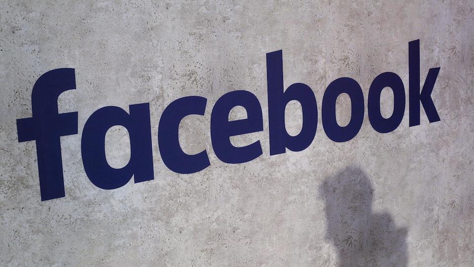 Une ombre passe devant le logo de Facebook sur un mur gris