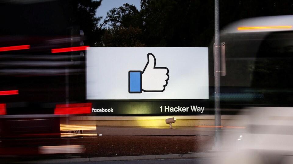 L'entrée du siège social de Facebook vu entre deux autobus en mouvement à Menlo Park, en Californie.