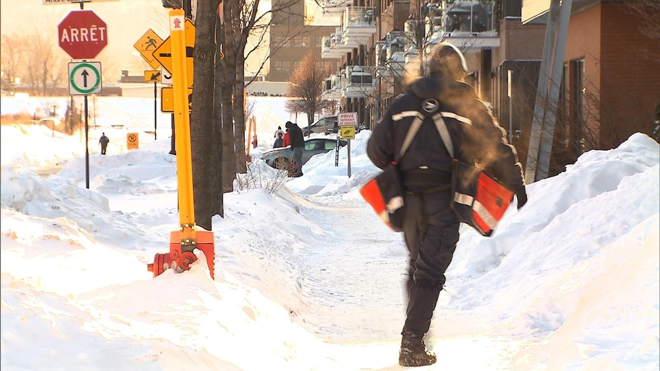 Un facteur livre le courrier dans la neige et le froid.