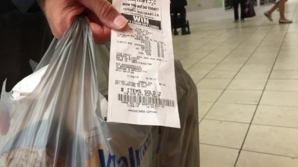 Un client montrant sa facture Walmart.