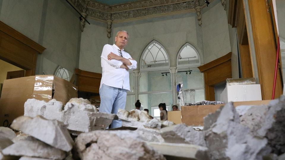 Un homme se tient debout dans sa maison. Des morceaux de pierre jonchent le sol.