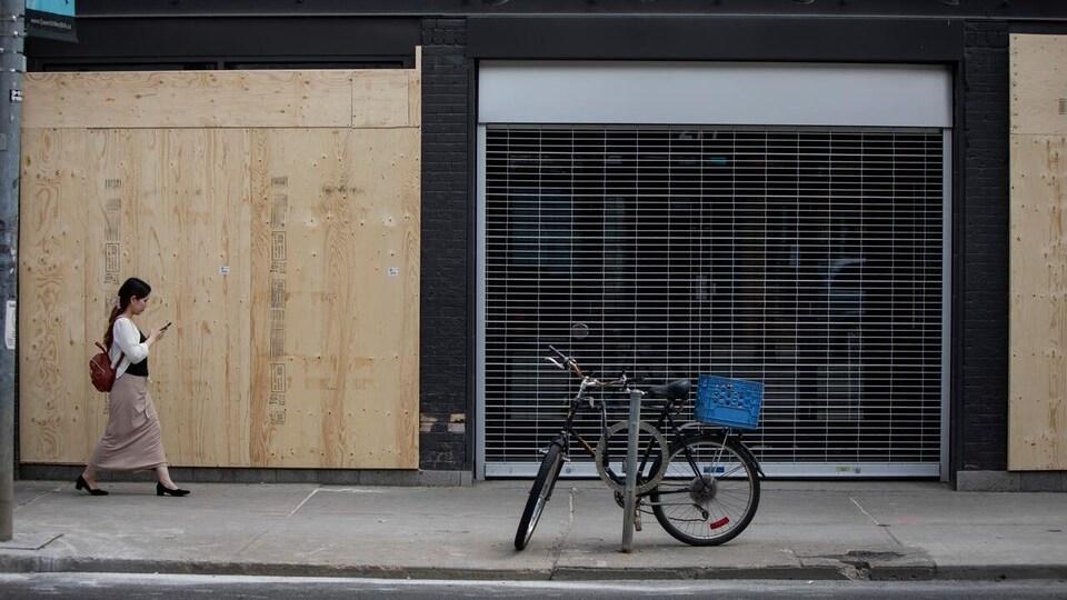 Une femme passe devant la façade d'un commerce placardé