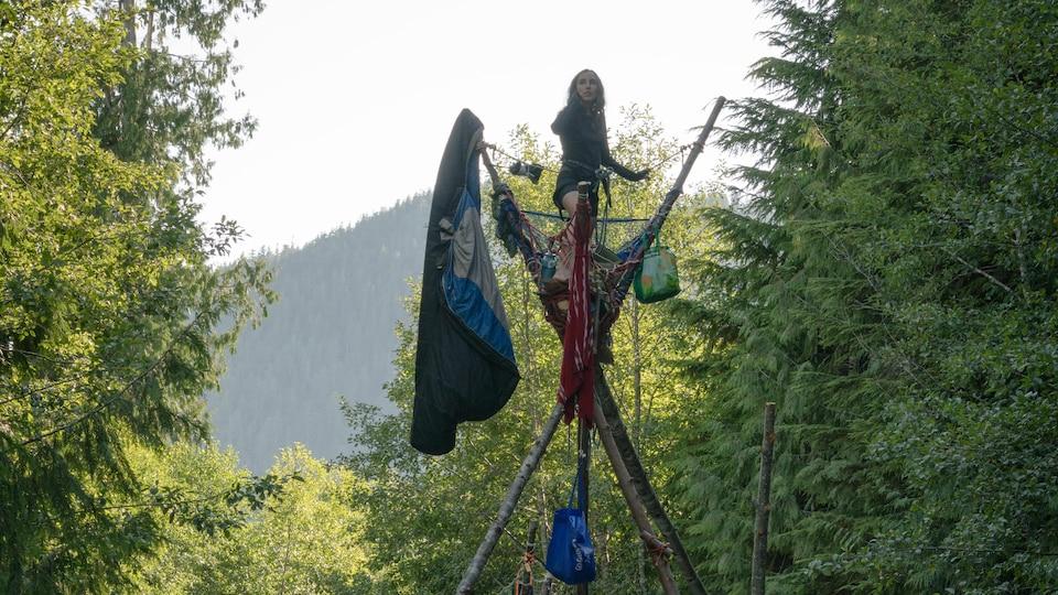 Une jeune femme perchée en haut d'un trépied.